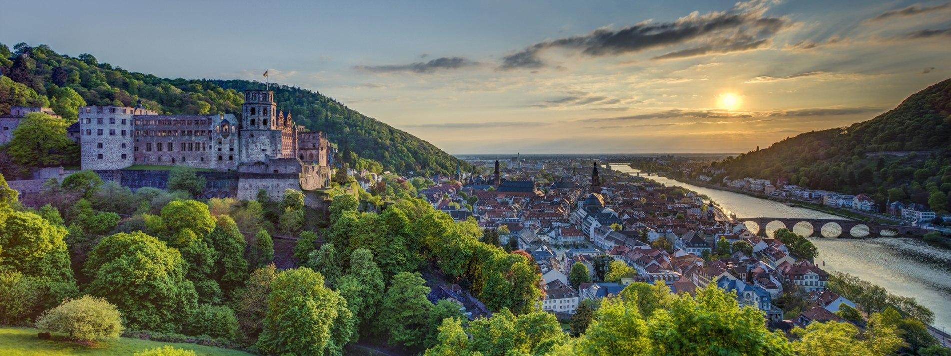 Aufnahme des Heidelberger Schlosses zwischen grünen Bäumen, Heidelberg ist im Hintergrund sichtbar - BAHNHIT.DE, © getty, Foto: Westend61